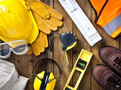 Personal protective workwear and blueprint with some measuring instruments shot directly from above on rustic wood background. The protective workwear includes hard hat, gloves, earmuff, goggles, steel toe shoes, and safety vest. The composition also includes a tape measure and bubble level and a construction blueprint, all items used by construction worker or engineer. Predominant colors: yellow and brown.
