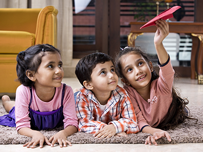 Happy children playing with toy paper airplane on carpet at home