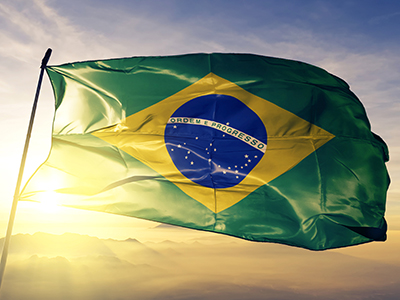 Brazil Brazilian flag on flagpole textile cloth fabric waving on the top sunrise mist fog